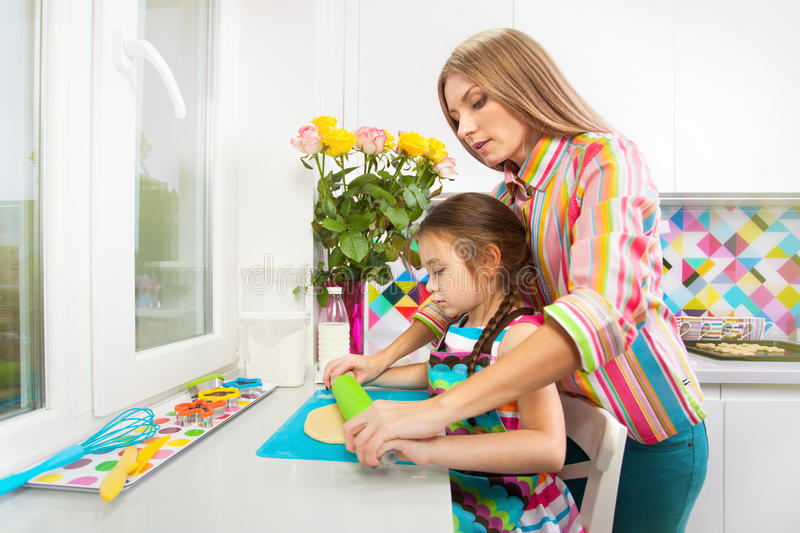 Little girl with her mother preparing a cookie on kitchen. Little girl with her mother preparing the dough for a cookie on kitchen. Family, children cooking royalty free stock photography
