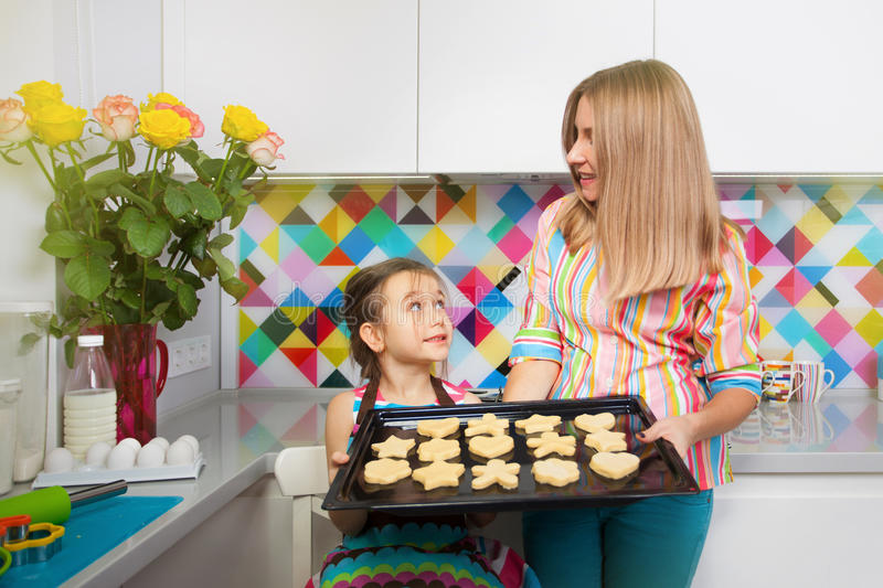 Little girl with her mother preparing a cookie on kitchen. Family, children cooking concept stock photo