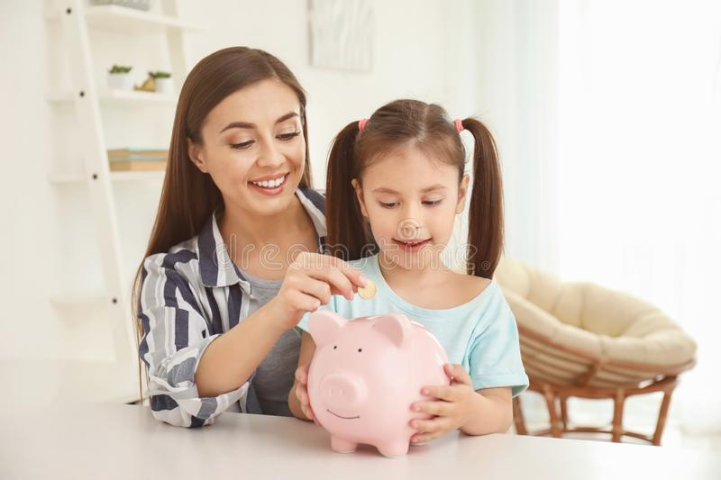 Little girl with her mother sitting at table and putting coin into piggy bank indoors. Money savings concept stock photography