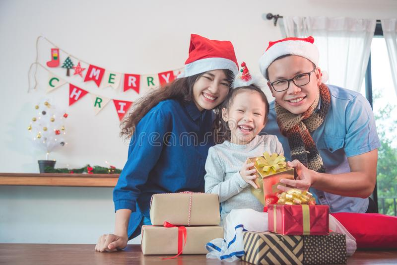 Little girl and her parents with christmas gift boxes. Little asian girl and her parents with christmas gift boxes smiling at home stock image