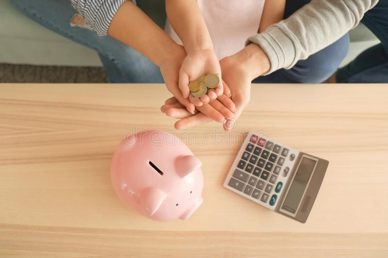 Little girl and her parents with coins and piggy bank at home. Money savings concept royalty free stock photo