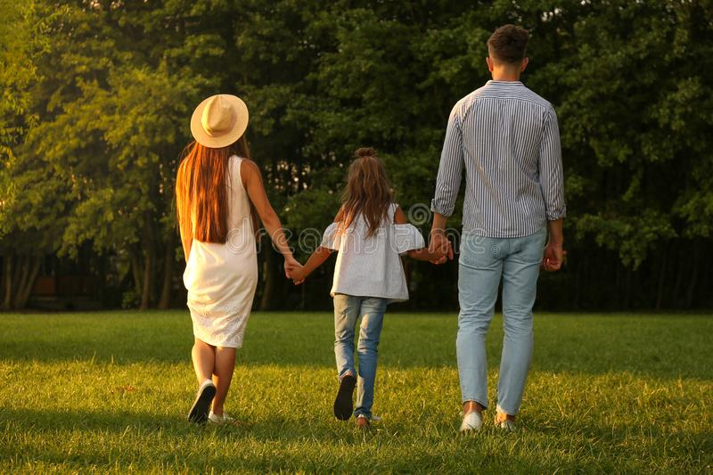 Little girl and her parents holding hands in park royalty free stock photo
