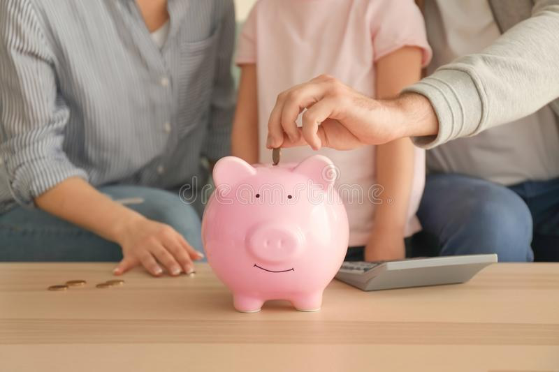 Little girl with her parents  putting coins into piggy bank indoors. Money savings concept royalty free stock image