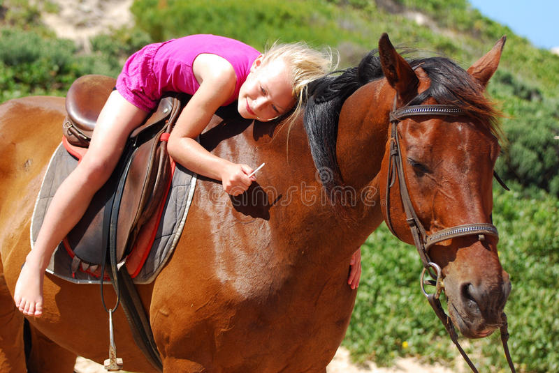 Little girl on her pony. A cute little smiling Caucasian girl child in a pink dress sitting on her brown pony and embracing it outdoors