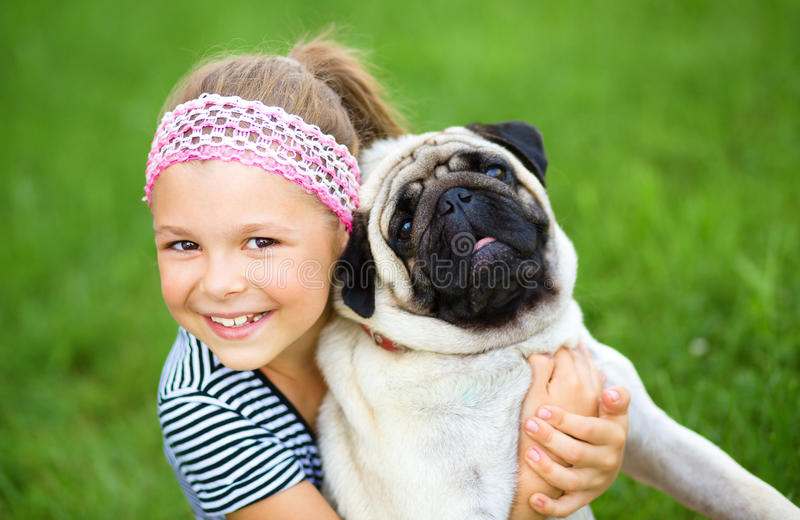 Little girl and her pug dog on green grass stock images