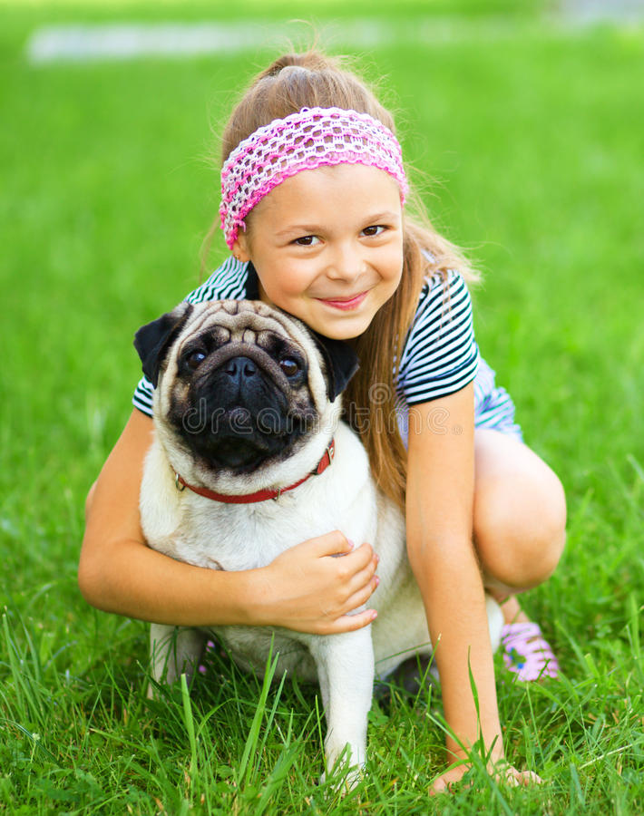 Little girl and her pug dog on green grass. Outdoor shoot royalty free stock image