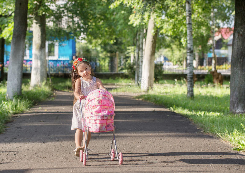 little girl with her toy carriage stock photo
