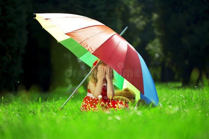 Little girl hid in a park under a rainbow umbrella. The image of a little girl hid in a park under a rainbow umbrella royalty free stock image