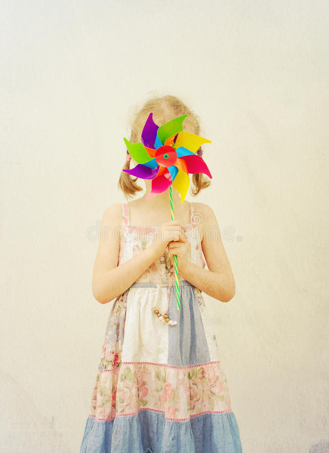 Little girl hides behind colorful pinwheel. royalty free stock images