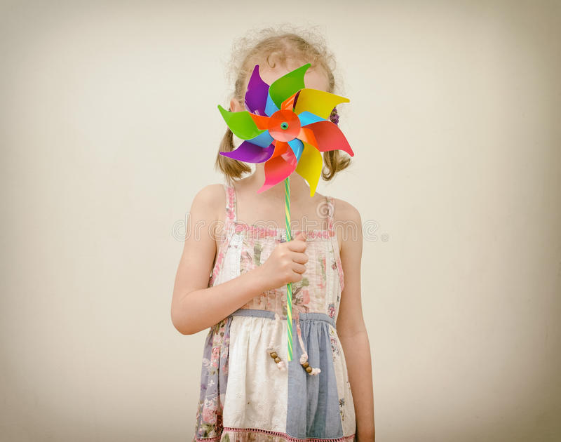 Little girl hides behind colorful pinwheel. stock image