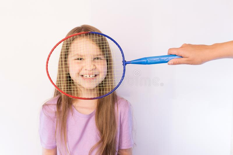Little girl hiding behind a badminton racket, smiling broadly, on a light background. For any purpose stock photos