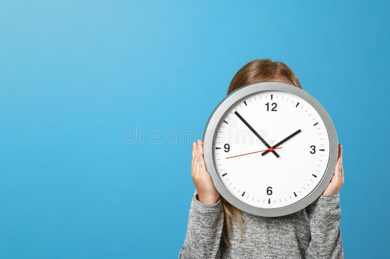 The little girl is hiding behind a big clock on a blue background. The concept of education, development, school, timing, time to stock photos