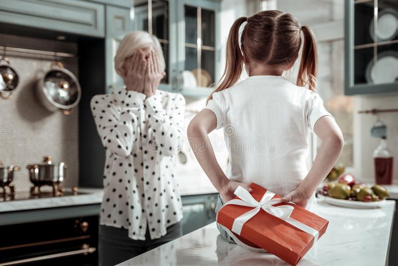 Little girl hiding big present and grandmother closing her eyes stock image