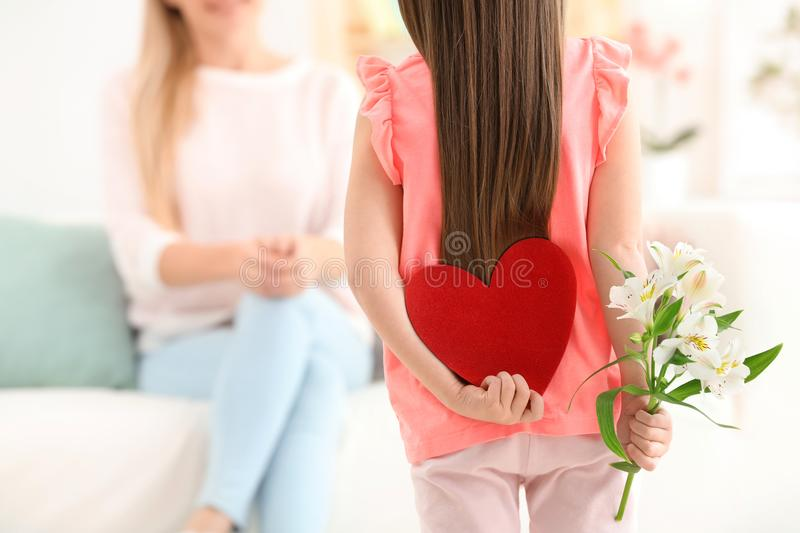 Little girl hiding felt heart and flower for Mother`s Day royalty free stock images