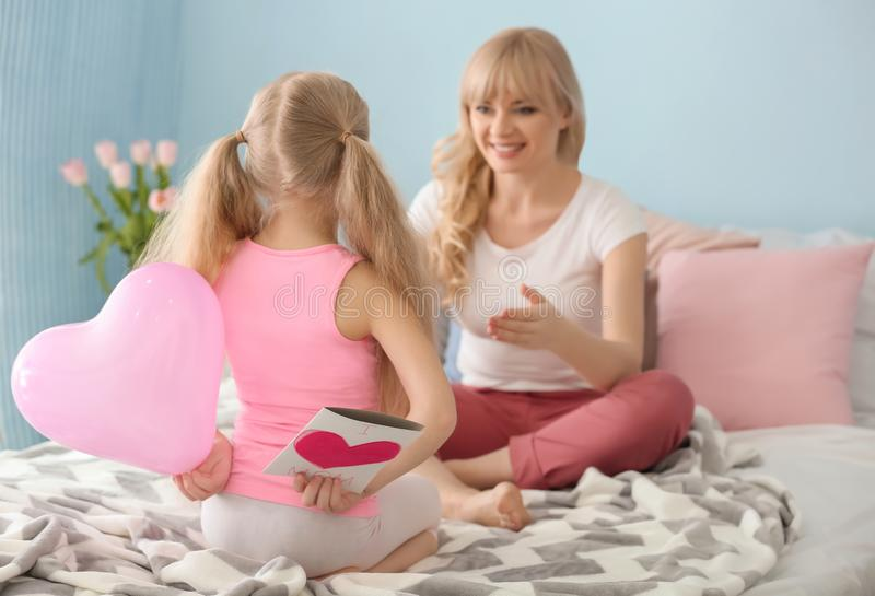 Little girl hiding handmade card and balloon for mother behind her back in bedroom stock photo