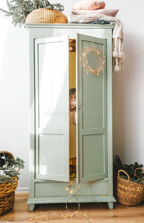 Free Little Girl Hiding Inside White Wardrobe Royalty Free Stock Photos - 168032688