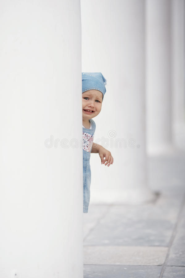 Little Girl Hiding In Columns Stock Images