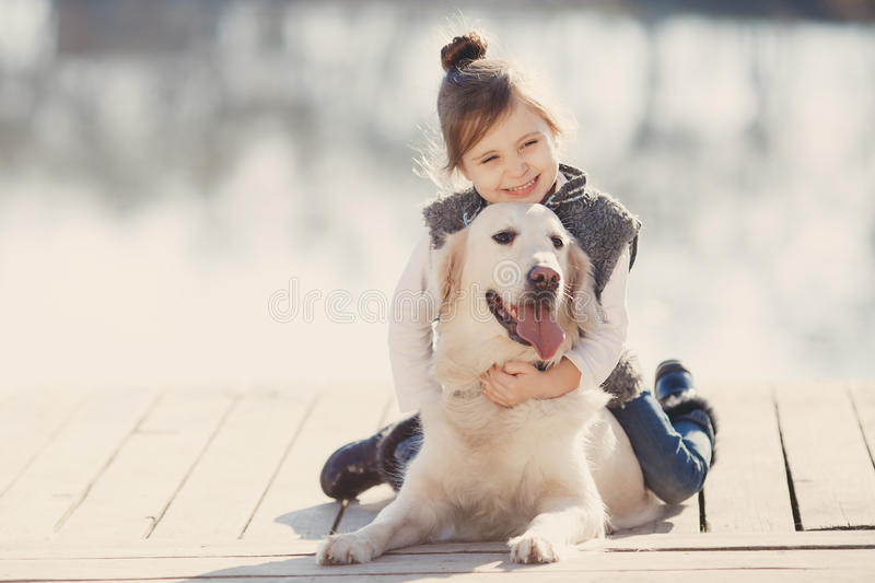 Little girl with his beloved dog at the lake stock images