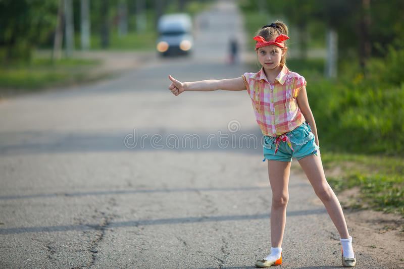 Little girl hitchhiking along a road. Travel. Little girl hitchhiking along a road royalty free stock photo