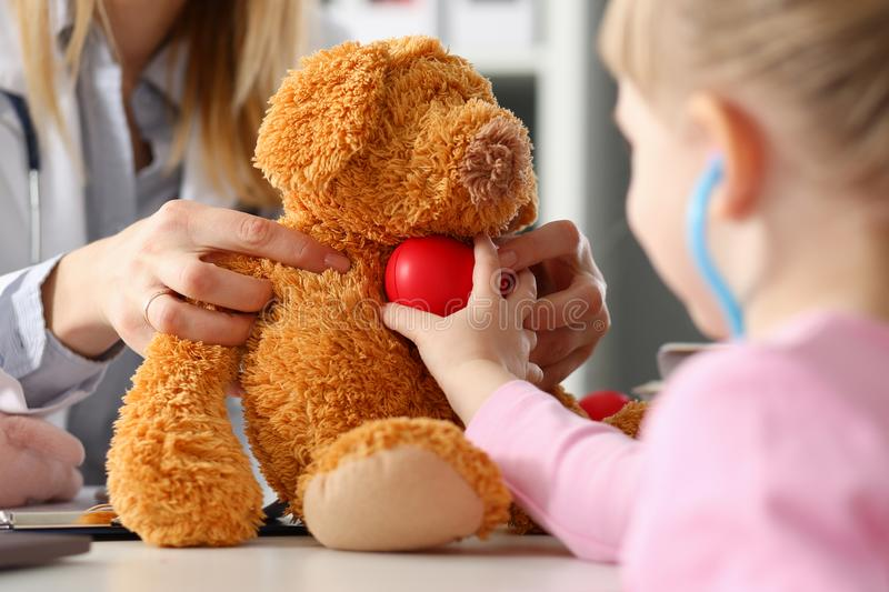 Little girl hold in arms toy red hear playing with teddy bear royalty free stock photo