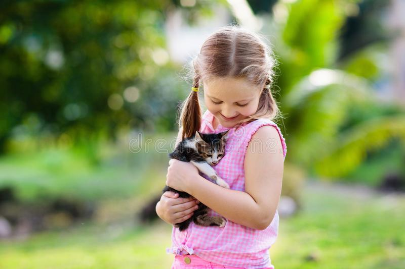 Little girl holding baby cat. Kids and pets royalty free stock images