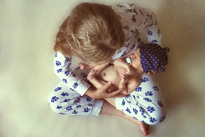 Little girl holding a baby stock photo