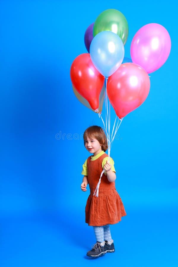 Little girl holding balloons stock photo