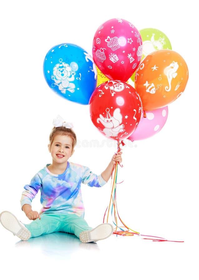 Little girl holding balloons stock photography