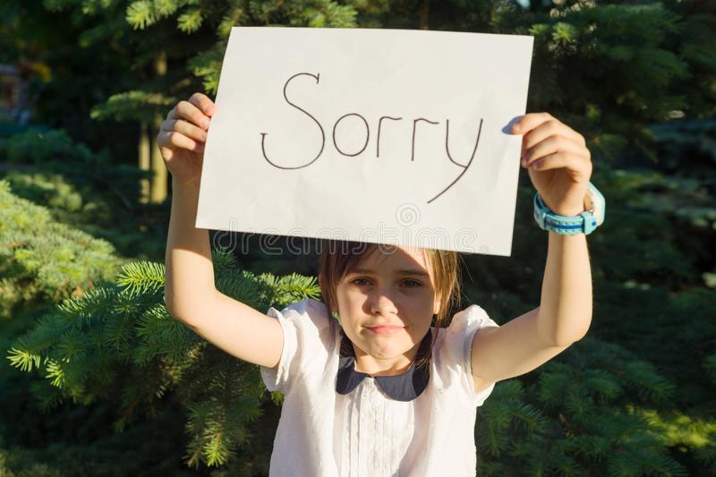 Little girl holding blank paper with message sorry.  stock image