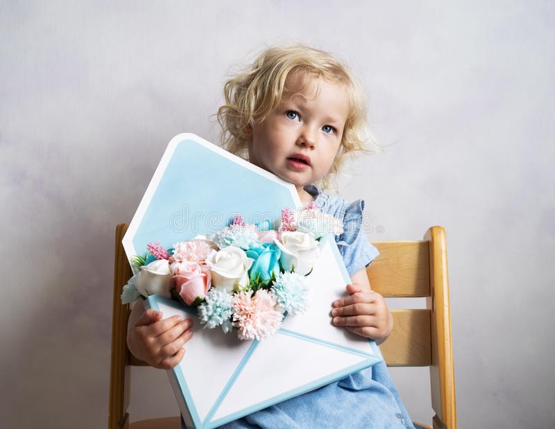 Little girl holding a bouquet of flowers in an envelope box. stock images