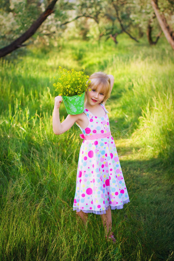 Little girl holding a bucket of flowers on shoulder royalty free stock images