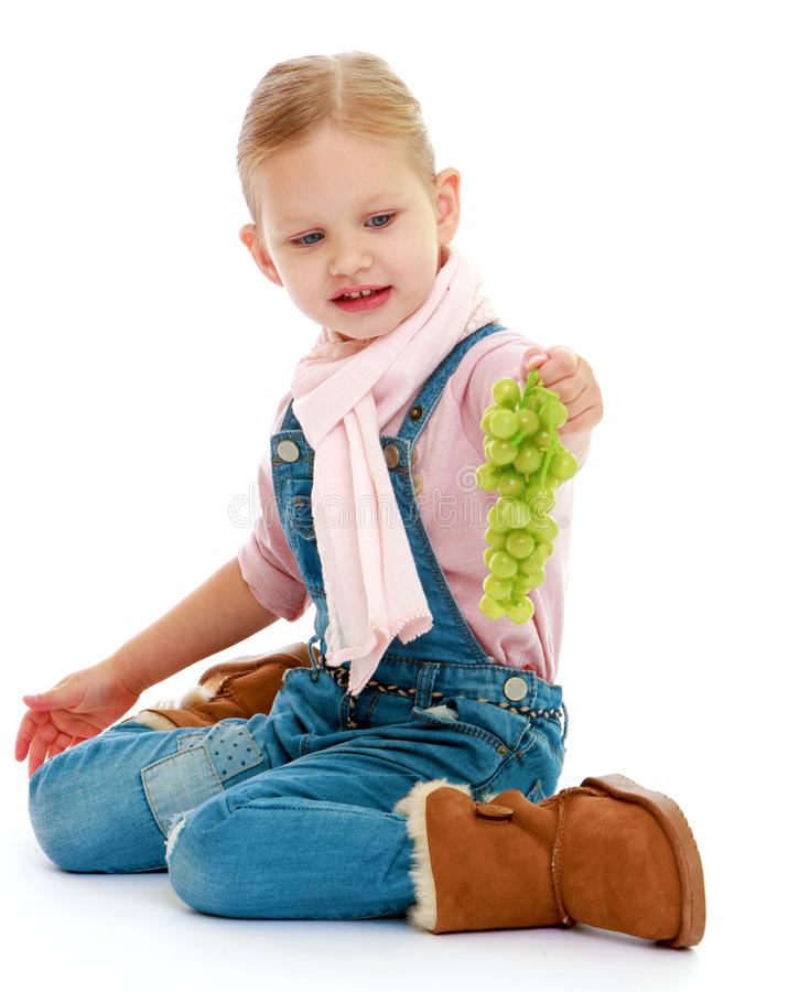 Little girl holding a bunch of grapes. royalty free stock images