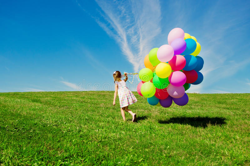 Little girl holding colorful balloons. Child playing on a green. Happy little girl holding colorful balloons. Child playing on a green meadow. Smiling kid stock photo