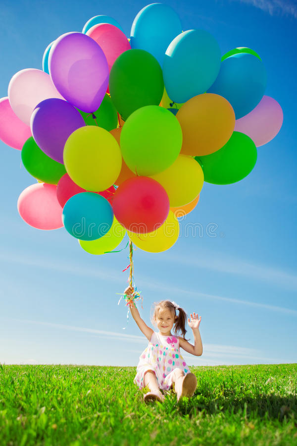 Little girl holding colorful balloons. Child playing on a green. Happy little girl holding colorful balloons. Child playing on a green meadow. Smiling kid stock photography