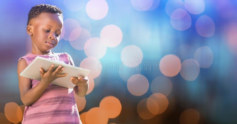 Little girl holding digital tablet over blur background royalty free stock photo