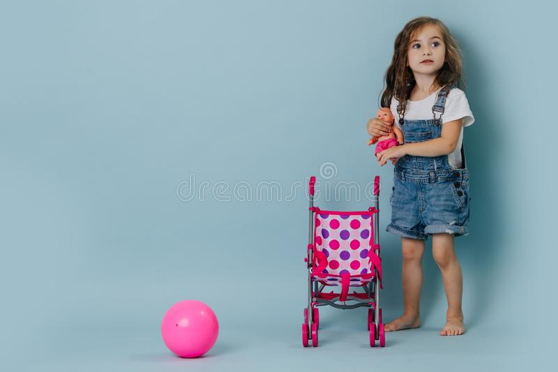 Little girl holding a doll next to a pram and pink gymnastic ball over blue royalty free stock image