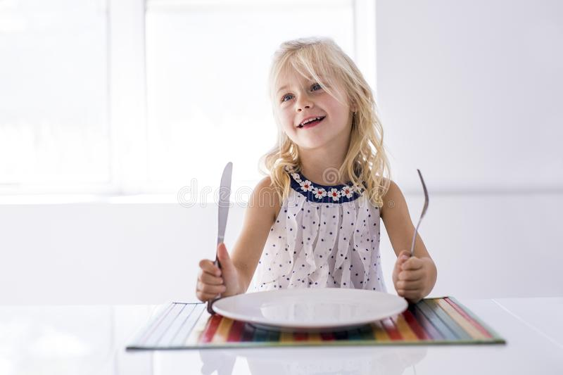 Little girl holding fork empty plate ready for food. royalty free stock photos