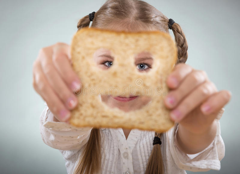 Little girl holding in front of his face, a happy slice of bread royalty free stock photography