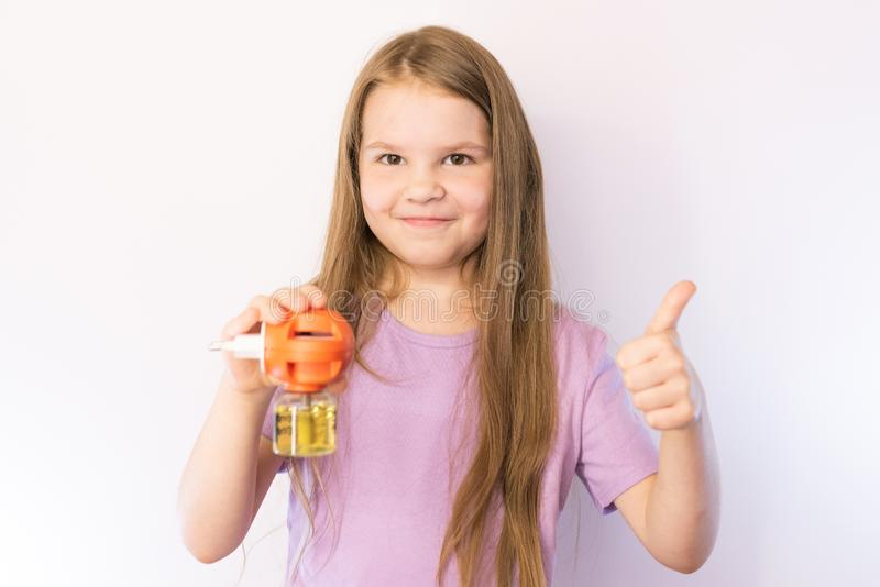 Little girl holding a fumigator from mosquitoes and the hand that shows the class, on a light background. For any purpose stock images
