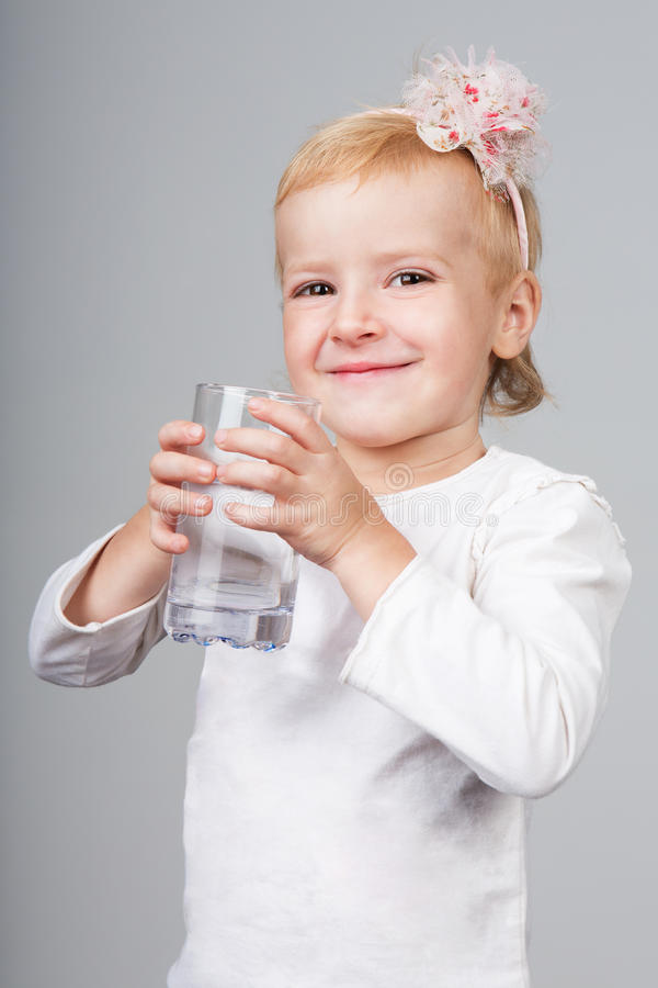 Little girl holding glass of water. Kid drink water on grey background. Girl drink water from a glass. Studio shot royalty free stock photos