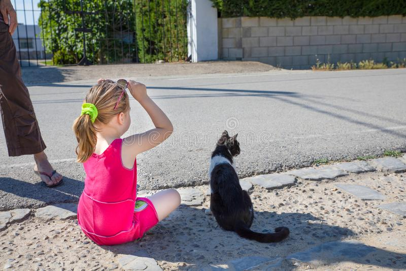 Little girl holding glasses and cat looking at the street royalty free stock images