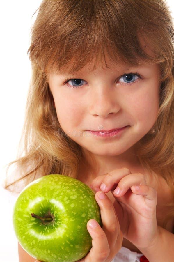 Little girl holding green apple stock images