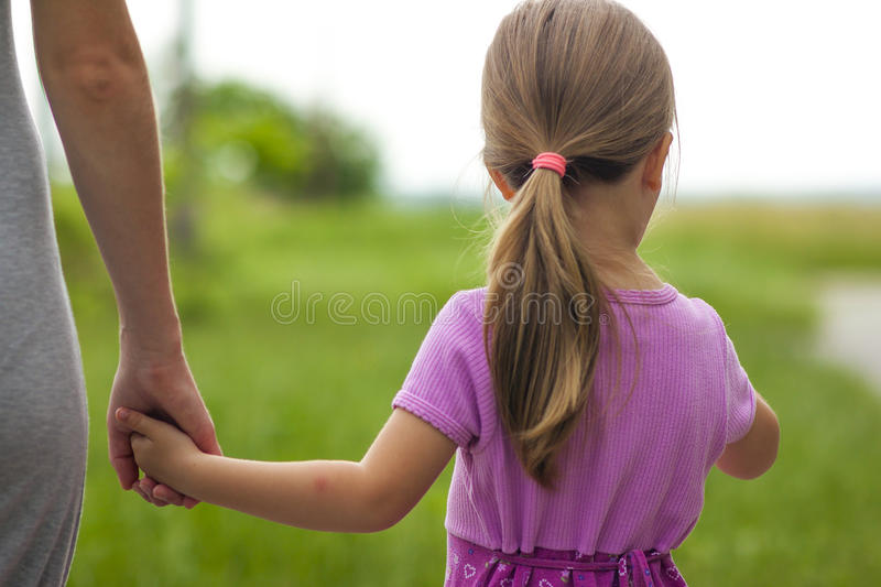 Little girl holding a hand of her mother. Family relations concept. royalty free stock photography