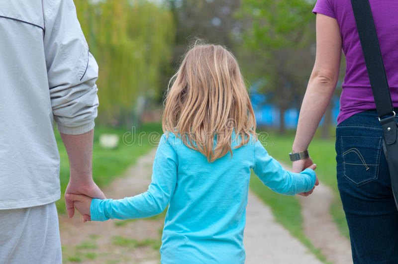 Little girl holding hands of her parents royalty free stock images