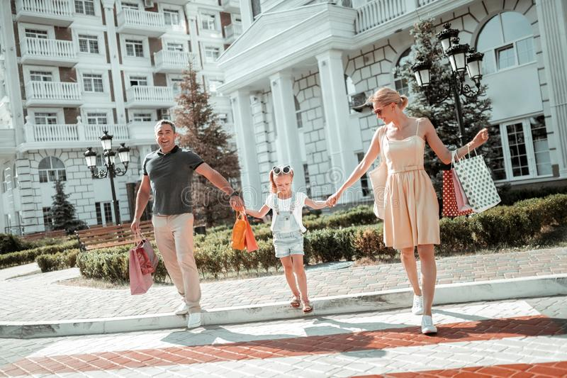 Little girl holding hands with her parents. Being careful. Little girl holding hands with her parents before crossing the road on their way home stock photo