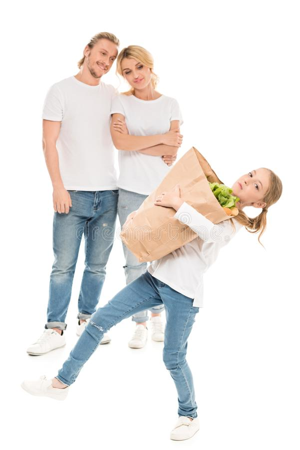 little girl holding heavy paper bag with food while parents standing behind stock photography