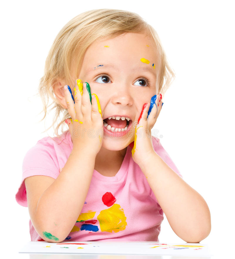 Little girl is holding her face in astonishment. While playing with paints, isolated over white royalty free stock images