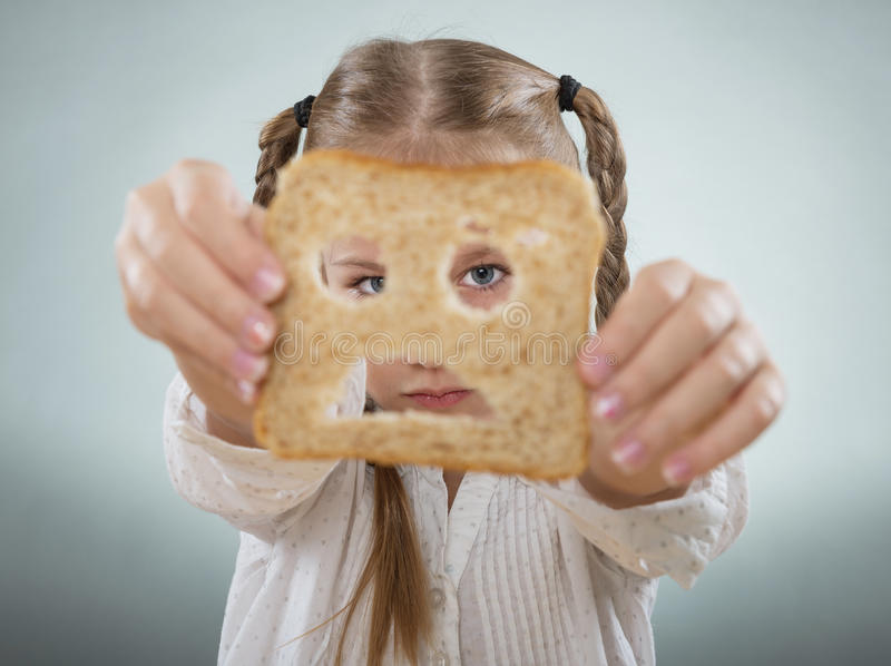 Little girl holding her face in front of a sad slice of bread royalty free stock image