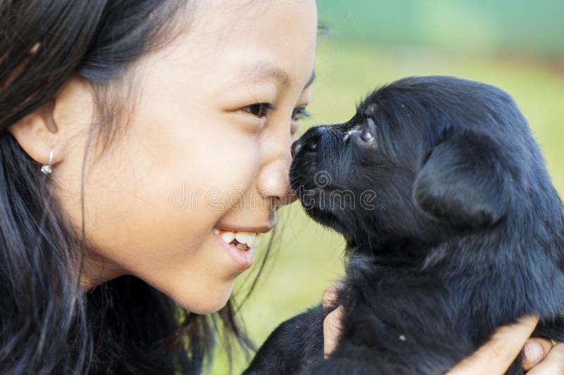 Little girl holding her puppy at outdoor. Close up of a little girl holding her puppy Labrador while playing at outdoor stock photography