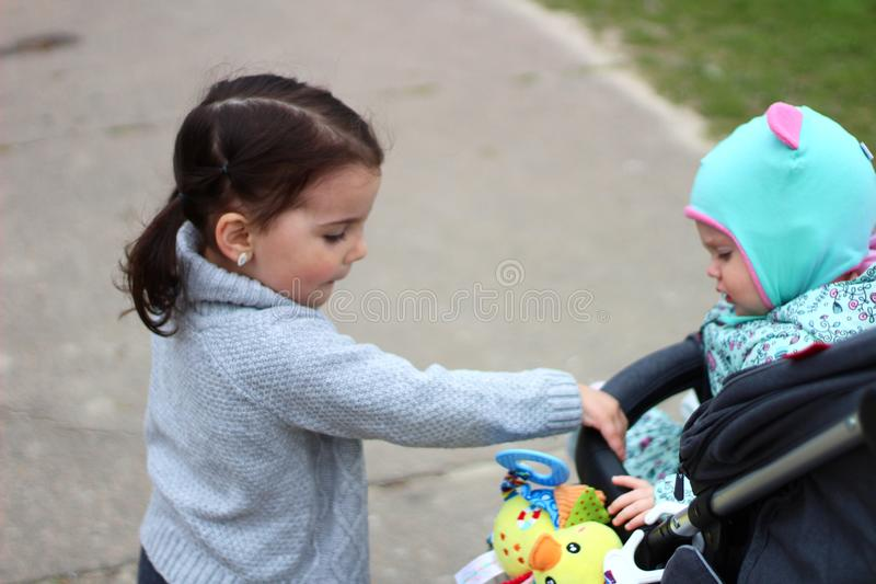 little girl holding her sister& x27;s hand in the pram royalty free stock photography